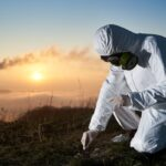 Scientist taking sample of ground at thermal power station.