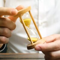 Businessman holds clock in hands. Concept of saving time and money. Time management. Planning work. Reduced cost and bureaucratic burden. Saving productivity. Extension of life. Debt / tax holidays